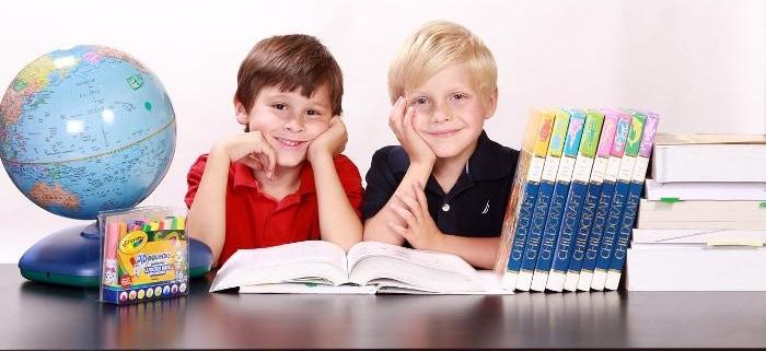 Foto di due bambini seduti dietro ad una scrivania.